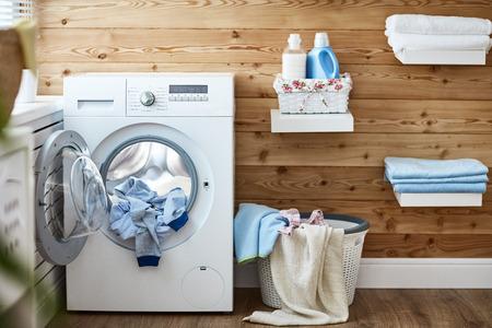 Interior de un lavadero real con una lavadora en la ventana en casa Foto de archivo - 84975599