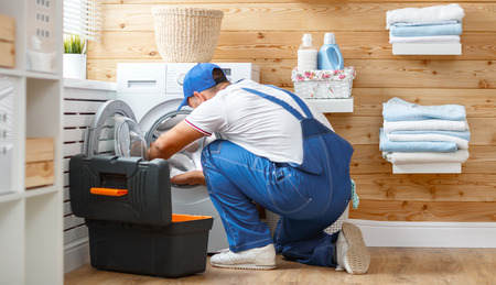 working man plumber repairs a washing machine in   laundry Imagens