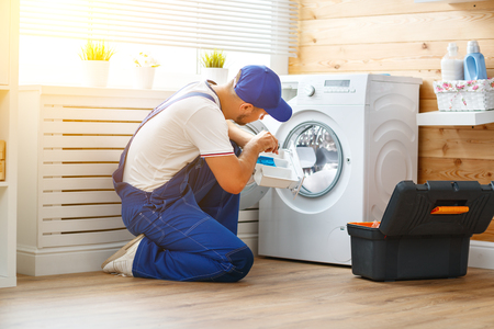 working man plumber repairs a washing machine in   laundry 스톡 콘텐츠