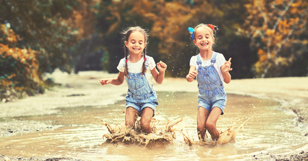 Happy funny sisters twins  child by girl jumping on puddles in rubber boots and laughing