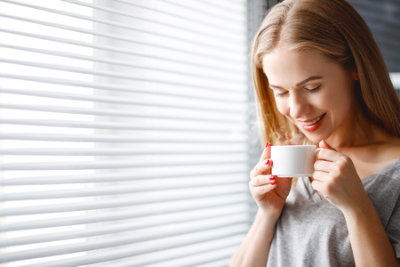 look latino: Happy young woman meets   morning with cup of coffee at window home
