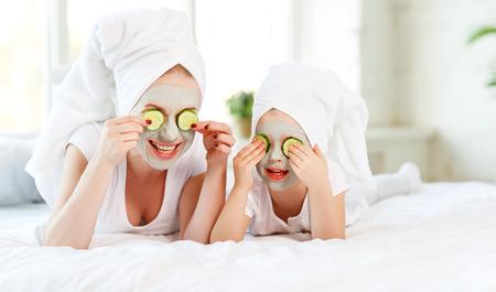 행복 한 가족 어머니와 아이 딸 머리에 수건으로 얼굴 피부 마스크를 확인