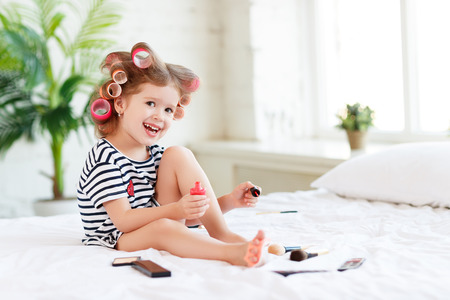 Happy funny child little girl with hair curlers does a pedicure, paints nails and laughs Stock Photo
