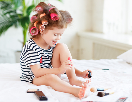 Happy funny child little girl with hair curlers does a pedicure, paints nails and laughs Фото со стока
