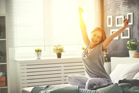 Jonge gelukkige vrouw werd in de ochtend in de slaapkamer bij het raam met haar rug wakker geworden