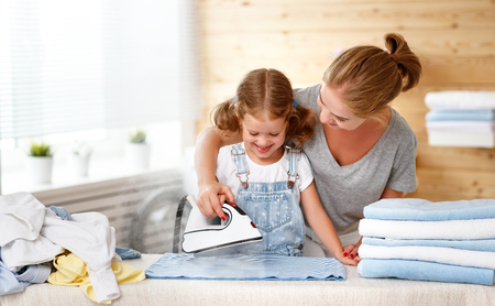 Happy family mother housewife and child daughter  ironing clothes iron in laundry at home  Reklamní fotografie