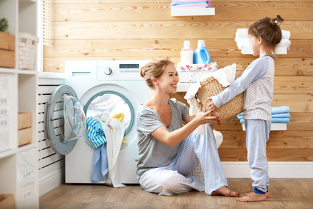 Happy family mother housewife and child daughter in laundry with washing machine  스톡 콘텐츠