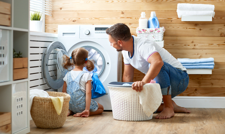 Happy family man father  householder and child daughter in laundry with washing machine Фото со стока - 85134855