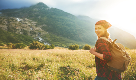 Woman tourist at the top of the mountain at sunset outdoors during a hike in summer Stock Photo