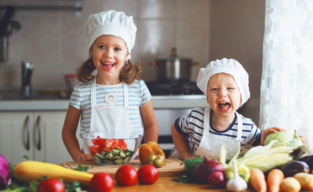 Healthy eating. Happy children prepares and eats vegetable salad in kitchen Banco de Imagens