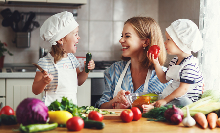 Healthy eating. Happy family mother and children  prepares   vegetable salad in kitchen 스톡 콘텐츠