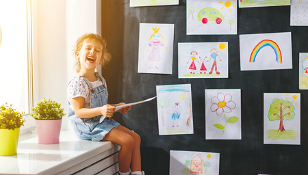drawings image: child girl hanging her drawings on the wall