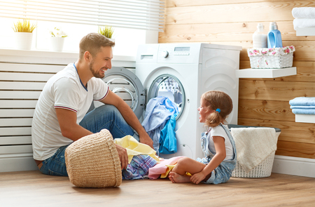 Happy family man father  householder and child daughter in laundry with washing machine Stockfoto