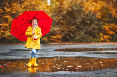 happy child girl with an umbrella and rubber boots on an autumn walk Standard-Bild