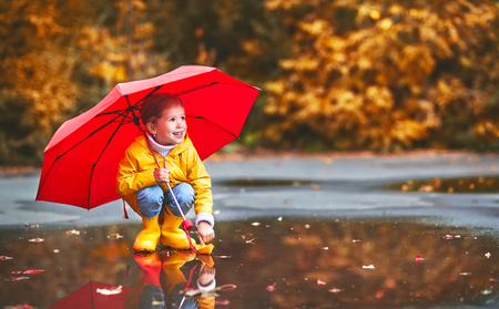 happy child girl with umbrella and paper boat in a puddle in   autumn on nature Imagens