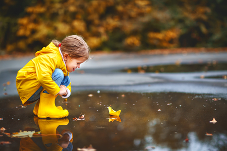 自然の秋の水たまりでの紙の船で幸せな子供女の子 写真素材