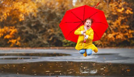 가 산책에 웅덩이에 우산과 고무 부츠와 함께 행복한 아이 소녀
