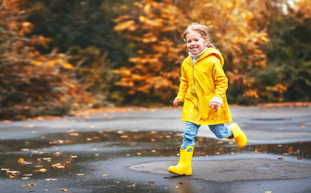 yellow: happy child girl with an umbrella and rubber boots in puddle on an autumn walk