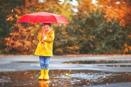 glückliches Kind Mädchen mit einem Regenschirm und Gummistiefeln in der Pfütze auf einem Herbstspaziergang