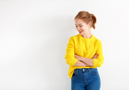 happy young woman in a yellow sweater on a white background Stock Photo