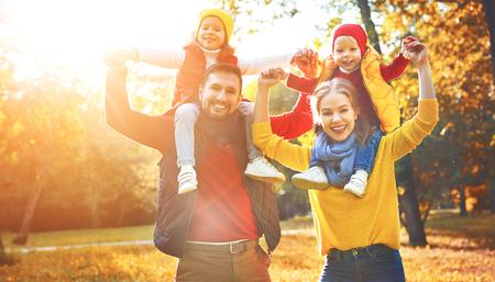 Feliz madre de la familia, el padre y los niños en un paseo de otoño en el parque Foto de archivo - 85566841