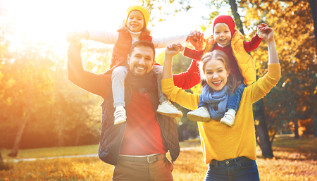 gelukkige familiemoeder, vader en kinderen op een herfstwandeling in het park