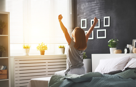 young happy woman woke up in the morning in the bedroom by the window with her back  Stok Fotoğraf