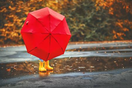 Niño feliz niña con un paraguas y botas de goma en el charco en un paseo de otoño Foto de archivo - 85503334
