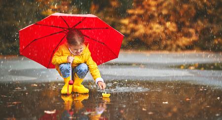 自然の秋の水たまりで傘と紙のボートを持つ幸せな子少女 写真素材