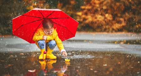 happy child girl with umbrella and paper boat in a puddle in   autumn on nature Foto de archivo