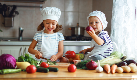 Healthy eating. Happy children prepares and eats vegetable salad in kitchen Stock Photo