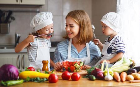Healthy eating. Happy family mother and children  prepares   vegetable salad in kitchen Standard-Bild