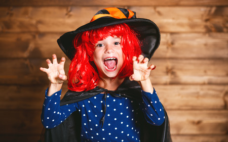 Laughing funny child girl in a witch costume in halloween Stock Photo