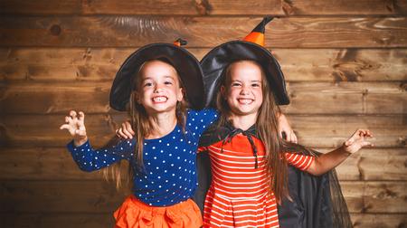 Lachende grappige kinderen zus tweeling meisje in een heks kostuum in halloween Stockfoto