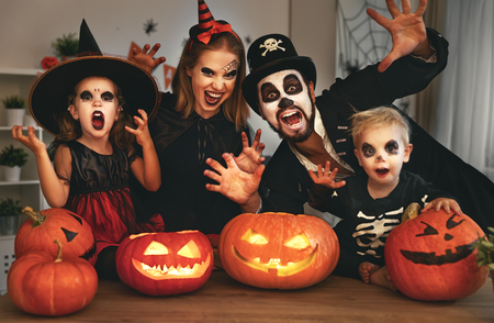 happy family mother father and children in costumes and makeup on a celebration of Halloween
