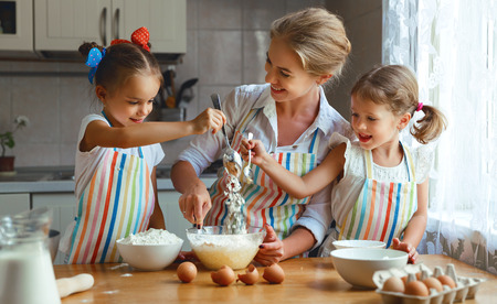 Happy family mother and children twins daughter bake kneading dough in the kitchen  Фото со стока