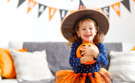 happy laughing child girl in witch costume to halloween Standard-Bild