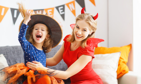 family mother and child girl daughter getting ready for halloween, putting on costumes