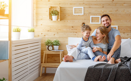 happy family mother, father and child daughter laughs in bed