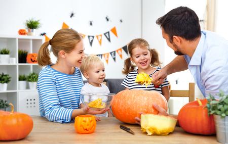 家族母父と子供たちはハロウィーンの休日のカボチャをカット
