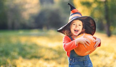 gelukkig kindmeisje met pompoen in openlucht in Halloween