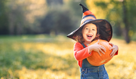 happy child girl with pumpkin outdoors in halloween