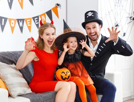 家でハロウィンの準備の衣装で幸せな家族