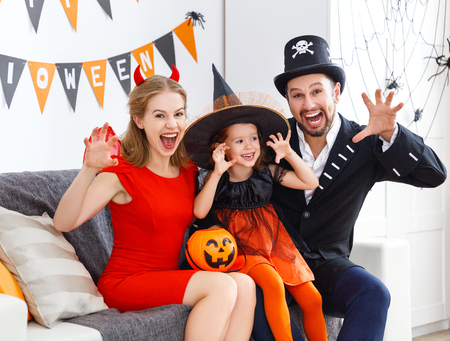 happy family in costumes getting ready for halloween at home  Stock Photo