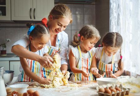 Glückliche Familie Mutter und Kinder Zwillinge Tochter backen Kneten Teig in der Küche Standard-Bild - 86615980