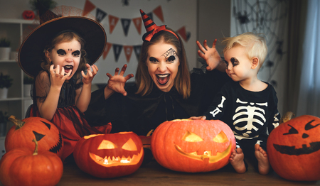 family mother and children in costumes and makeup to halloween with pumpkin in   dark at home