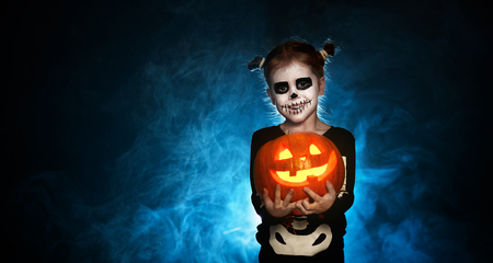 magic skeleton with a pumpkin. baby girl in costume to halloween