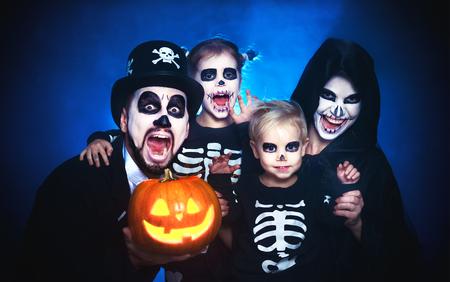padre de la familia de la familia feliz y los niños en trajes y maquillaje en una celebración de Halloween