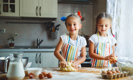 happy sisters children girls bake cookies, knead dough, play with flour and laugh in the kitchen Stock fotó - 86950252