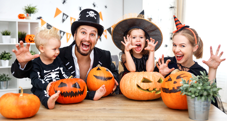 skeleton costume: happy family mother father and children in costumes  on a celebration of Halloween